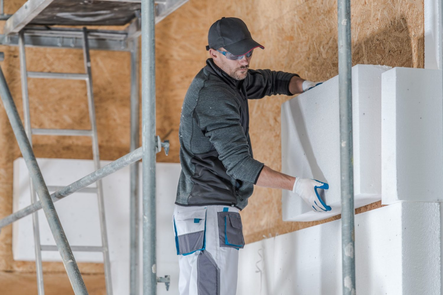 Construction Industry. Caucasian Insulation Installer Contractor in His 30s Working on a Scaffolding.